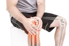 Equipaggi la sofferenza con il dolore del ginocchio mentre si siedono contro il fondo bianco immagine stock libera da diritti