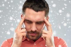 Equipaggi la sofferenza dal dolore capo o il pensiero sopra la neve Fotografia Stock Libera da Diritti