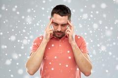 Equipaggi la sofferenza dal dolore capo o il pensiero sopra la neve Fotografia Stock