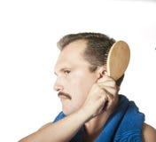 Equipaggi la spazzolatura dei suoi capelli nello specchio del bagno. Fotografia Stock