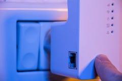 Equipaggi la stampa con il suo dito sul bottone di WPS sul ripetitore di WiFi che i fotografia stock