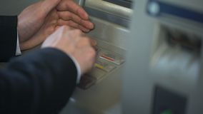Equipaggi la tastiera nascondentesi del Bancomat mentre inseriscono il suo codice del perno stock footage
