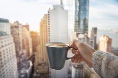 Equipaggi la tazza di caffè della tenuta in appartamenti di lusso dell'attico con la vista a New York immagini stock