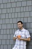 Equipaggi la tendenza contro una parete che tiene una tazza da caffè Fotografie Stock