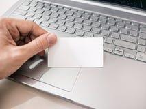 Equipaggi la tenuta del biglietto da visita bianco in bianco e per mezzo del computer portatile Fotografia Stock