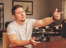 Equipaggi la tenuta del controllo del gioco ed indicare il dito come una pistola Fotografia Stock