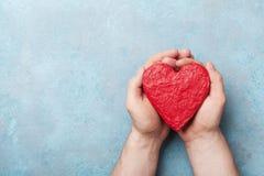 Equipaggi la tenuta del cuore rosso nella vista superiore delle mani Concetto sano, di amore, dell'organo di donazione, del donat fotografia stock