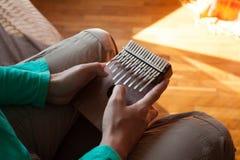Equipaggi la tenuta del kalimba africano tradizionale dello strumento musicale in una mani del ` s Uomo che gioca su un kalimba c Immagine Stock Libera da Diritti