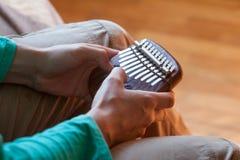 Equipaggi la tenuta del kalimba africano tradizionale dello strumento musicale in una mani del ` s Uomo che gioca sul kalimba Fotografia Stock Libera da Diritti