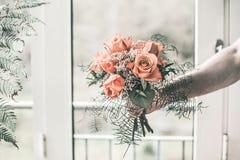 Equipaggi la tenuta del mazzo festivo bello sulle sue armi stese contro lo sfondo della finestra e delle foglie delle piante fotografie stock