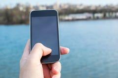 Equipaggi la tenuta del telefono cellulare con il fiume nei precedenti Fotografia Stock Libera da Diritti