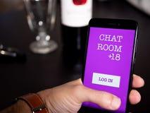 Equipaggi la tenuta del telefono con chiacchierata app in ristorante fotografia stock libera da diritti