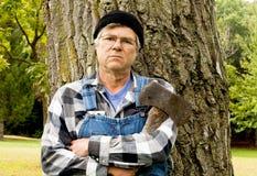 Equipaggi la tenuta dell'ascia che si appoggia contro un albero Fotografia Stock Libera da Diritti