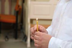 Equipaggi la tenuta della candela bruciante in una chiesa Immagini Stock