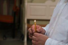 Equipaggi la tenuta della candela bruciante in una chiesa Fotografia Stock Libera da Diritti