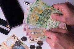 Equipaggi la tenuta delle banconote rumene dei leu, primo piano su fondo bianco Immagine Stock