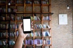 Equipaggi la tenuta dello schermo in bianco di uno smartphone alla biblioteca immagine stock libera da diritti