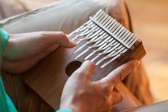 Equipaggi la tenuta di grande kalimba dello strumento musicale africano tradizionale in una mani del ` s Uomo che gioca sul kalim Fotografia Stock Libera da Diritti