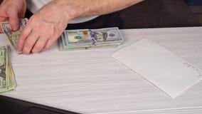 Equipaggi la tenuta e contanti dare a qualcuno sulla vecchia tavola di legno, concetto di affari Banconota degli Stati Uniti dei  video d archivio