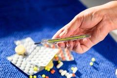 Equipaggi la tenuta il termometro a mercurio e delle droghe medici in un fondo Fotografie Stock