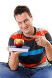 Equipaggi la tenuta un libro e dell'una mela rossa Immagine Stock