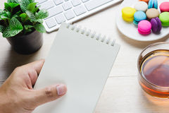 Equipaggi la tenuta un libro e della tastiera con una tazza calda di tè, maccherone sulla tavola fotografie stock libere da diritti