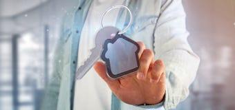 Equipaggi la tenuta una chiave e della rappresentazione della casa 3d Immagine Stock Libera da Diritti