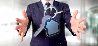 Equipaggi la tenuta una chiave e della rappresentazione della casa 3d Immagine Stock