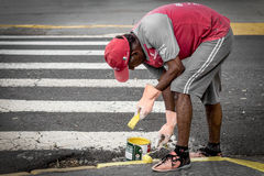 Equipaggi la verniciatura del marciapiede con un pennello Fotografie Stock Libere da Diritti