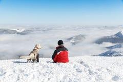 Equipaggi la viandante ed il suo cane su una cima della montagna Immagini Stock Libere da Diritti