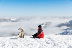 Equipaggi la viandante ed il suo cane su una cima della montagna Immagini Stock