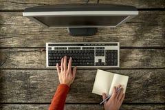 Equipaggi lavorare ad un computer ad una tavola rustica Immagine Stock