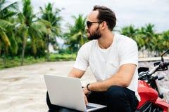 Equipaggi lavorare al computer portatile mentre si siedono sul suo motociclo Fotografia Stock Libera da Diritti