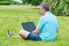 Equipaggi lavorare al suo computer portatile nella sosta Immagini Stock Libere da Diritti