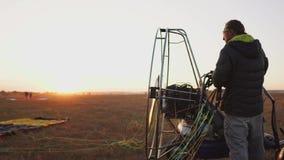 Equipaggi le correzioni pilota dell'aliante del motore il paracadute al corpo dell'aliante al tramonto nel campo archivi video