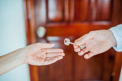 Equipaggi le elasticità della mano del ` s una femmina di chiave su fondo della porta di legno Affare con il concetto del bene im Immagini Stock Libere da Diritti