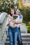 Equipaggi le elasticità la sua giovane moglie incinta un mazzo fotografia stock libera da diritti