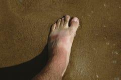 Equipaggi le gambe del ` s sulle onde del mare e della spiaggia di sabbia Fotografia Stock