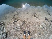 Equipaggi le gambe in scarpe che stanno vicino alla linea di acqua e di terra del lago con la riflessione della montagna in laghi immagine stock libera da diritti
