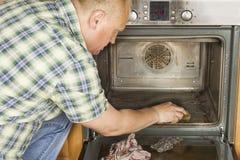 Equipaggi le genuflessioni sul pavimento nella cucina e pulisce il forno Immagine Stock