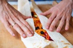Equipaggi le mani che preparano l'alimento - burrito vegetariano con le verdure, le olive, la carota, il peperone dolce, pomodori Fotografia Stock Libera da Diritti