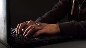 Equipaggi le mani che scrivono sulla tastiera di computer portatile, attacco del pirata informatico Fotografie Stock