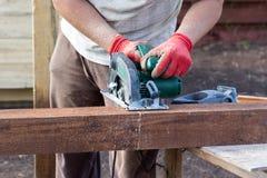 Equipaggi le mani che tagliano il fascio di legno con la sega circolare Immagini Stock Libere da Diritti
