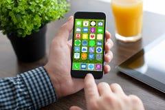 Equipaggi le mani che tengono il telefono con i apps delle icone dello schermo domestico Immagini Stock Libere da Diritti