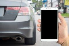 Equipaggi le mani che tengono lo Smart Phone con il parcheggio delle automobili della sfuocatura Fotografia Stock