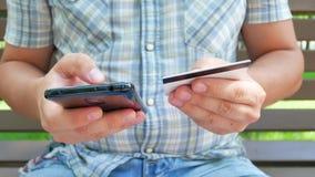Equipaggi le mani che tengono lo smartphone nero ed il debito o la carta di credito archivi video
