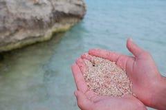 Equipaggi le mani che tengono un pezzo della sabbia rosa Fotografia Stock Libera da Diritti