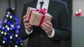 Equipaggi le mani del ` s che armeggiano un regalo di Natale archivi video