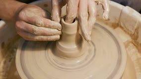 Equipaggi le mani del ` s che fanno gli articoli dell'argilla sulla ruota del ` s del vasaio stock footage