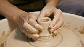 Equipaggi le mani del ` s che fanno gli articoli dell'argilla sulla ruota del ` s del vasaio video d archivio